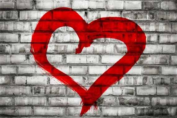 Heart shape love symbol painted on old brick wall background
